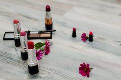 为构成汇集设置的化妆用品:面粉,唇膏,染睫毛油刷子,指甲油,脸红,眼影 库存照片