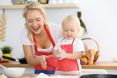 为母亲` s天照顾和她的烹调假日饼或曲奇饼的小女儿 愉快的家庭的概念在厨房里 免版税库存照片