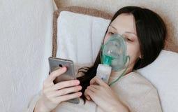 为治疗使用雾化器和吸入器 吸入通过吸入器面具的少妇说谎在长沙发和聊天 免版税库存照片