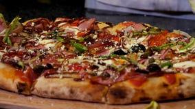 为洒可口比萨的手关闭与帕尔马干酪,意大利料理概念 ?? 厨师手投入 库存图片