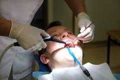 为漂洗牙的牙齿工具 清洗的牙,牙齿卫生学 牙医是漂洗有清洁工具浪花的耐心牙 库存照片