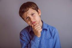 为灰色背景认为的少年男孩 免版税库存图片