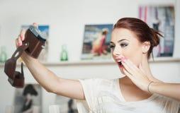 为照相的美丽,微笑的红色头发妇女与照相机 采取自画象的时兴的可爱的女性 免版税库存照片