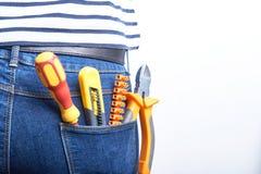 为电工的工具妇女穿的蓝色牛仔裤的后面口袋的 螺丝刀、切削刀和托架 图库摄影