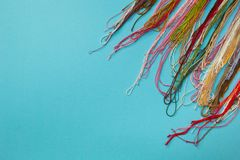 为编织在蓝色镶边背景的衣裳使用的多色的毛线 库存图片