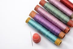 为缝合,与螺纹的多彩多姿的卷,针和顶针设置在白色背景 免版税库存照片