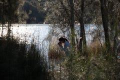 为自然照相的女孩在河岸 库存照片
