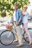 去为自行车的愉快的成熟夫妇在城市乘坐 图库摄影