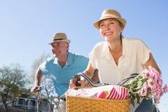 去为自行车的愉快的资深夫妇在城市乘坐 免版税库存照片