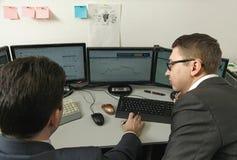 为计算机的两个人在办公室参与换 库存照片