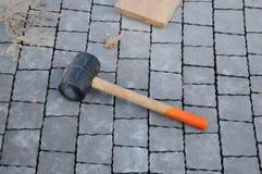 为遏制的石头和放下砖的路面,橡胶短槌的泥工工具 瓦片的橡胶锤子 免版税库存图片
