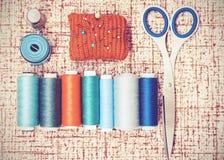 为针线、红色被编织的针垫缝合的,剪刀和色的螺纹卷的工具在与拷贝空间的棕色背景为 库存照片