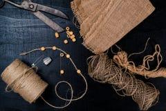 为针线设置:剪刀,与一条绳索的亚麻制织品在黑背景 顶视图 库存照片