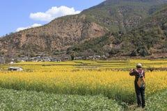 为长江的第一个弯的游人油菜花附近的石鼓村庄照相 免版税库存照片