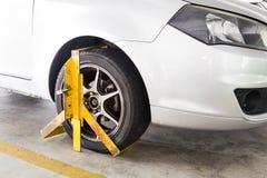 为非法停车处侵害夹紧的车轮在停车场 免版税图库摄影
