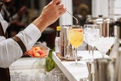 为鸡尾酒服务的侍酒者的手 与果子切片的橙色鸡尾酒在酒吧柜台 库存图片