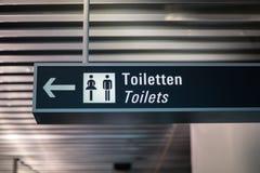 为洗手间/休息室签字在机场(用德语和英语) 库存图片