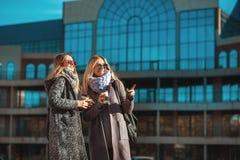 为购物准备!喝咖啡的两名美丽的妇女画象,当走室外时 免版税库存图片