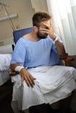 为他的卫生状况伤害了人哭泣在医房坐单独哭泣在痛苦中担心的年轻人 免版税库存图片