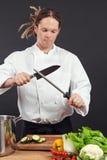 主厨削尖他的刀子 免版税库存照片