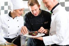 主厨小组在餐馆厨房里用点心 免版税图库摄影