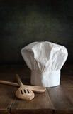 主厨帽子和wodden在木头的匙子 免版税库存照片