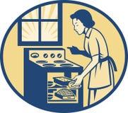 主妇在减速火箭烤箱的火炉的贝克烘烤 免版税库存照片
