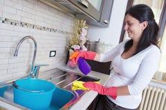 主妇清洁家具在厨房里 免版税库存图片