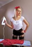 主妇电烙她的女衬衫 免版税库存图片