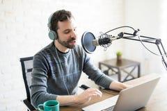 主持一台网上收音机的无线电节目播音员 库存图片