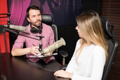 主持与妇女的无线电赠送者一次采访在演播室 免版税图库摄影