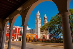 主要公园的看法通过图书馆建筑的曲拱在坎比其,墨西哥 在背景中是大教堂del浓缩的la 免版税库存图片