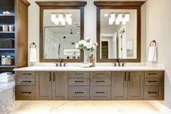 主要卫生间内部在有黑暗的硬木内阁、白色木盆和玻璃门阵雨的豪华现代家 免版税库存照片