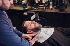 主要美发师面孔为刮在理发店做准备 免版税图库摄影