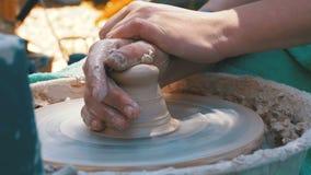 主要陶瓷工和花瓶的手在陶瓷工` s的黏土转动特写镜头 影视素材