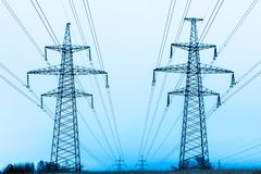 主输电线在背景天空蔚蓝和有导线的森林塔在冬天乡下领域的 免版税库存图片