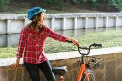 主题生态运输方式自行车 佩带一支蓝盔部队和长发姿势的美丽的年轻kasazy妇女其次站立 免版税库存图片
