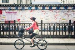 丽江,中国- 2015年6月21日::妇女在利嘉中的骑一辆自行车 免版税库存图片