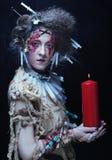 举一个蜡烛的少妇佩带的狂欢节服装 免版税库存照片