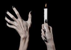举一个蜡烛的手,一个蜡烛被点燃,黑背景,孑然,温暖,在黑暗,递死亡,手巫婆 免版税库存照片