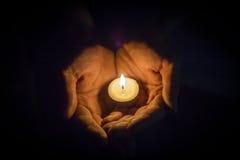 举一个蜡烛的手 库存图片