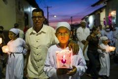 举一个蜡烛的年轻男孩在一支队伍的晚上在市的街道利昂在尼加拉瓜在复活节庆祝期间 库存照片