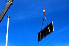 举一台大太阳能集热器的起重机 免版税库存图片