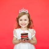 举一点蛋糕和蜡烛的白肤金发的女孩 免版税库存图片