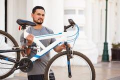 举一辆自行车的男性骑自行车者在城市 库存图片