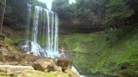 举到吸引力在瀑布和女孩附近石头的 影视素材