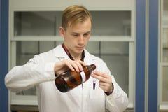 举办一个化学反应的化学家 免版税库存图片