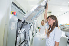举在专业洗衣店的夫人门户开放主义的机器 免版税图库摄影