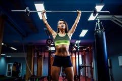 举在健身房的妇女重量crossfit 健身妇女deadlift杠铃 库存图片