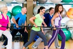 举在健身房的男人和妇女杠铃 免版税库存照片